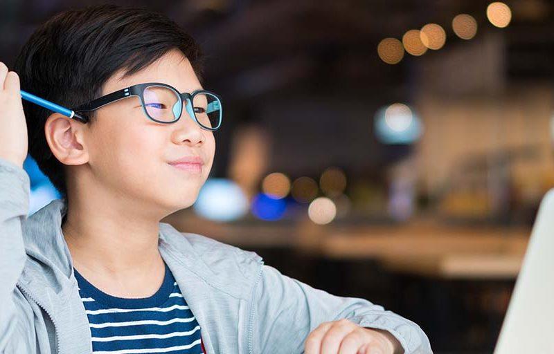 Smart looking Asian preteen boy with eye blue light blocking gla